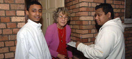 2 young Asian male volunteers, helping an old lady filling in a form, on her front door
