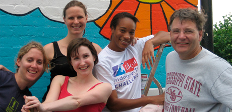 Volunteers smiling, after a cleaning activity, with a painted wall in the background with a smiley sun and clouds