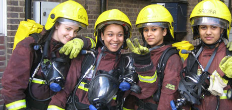 Four girls, volunteering with the Fire brigade, wearing fire fighter gear, with yellow helmets, smiling