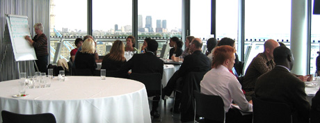 GLV network day, bright room with view over London, a facilitator writes on a flipchart, participants sitting around a table looking at the flipchart, with a second group of participants talking